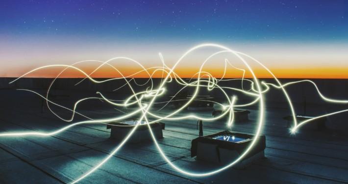 Light Painting auf den Dächern der Stadt vor dem Nachthimmel